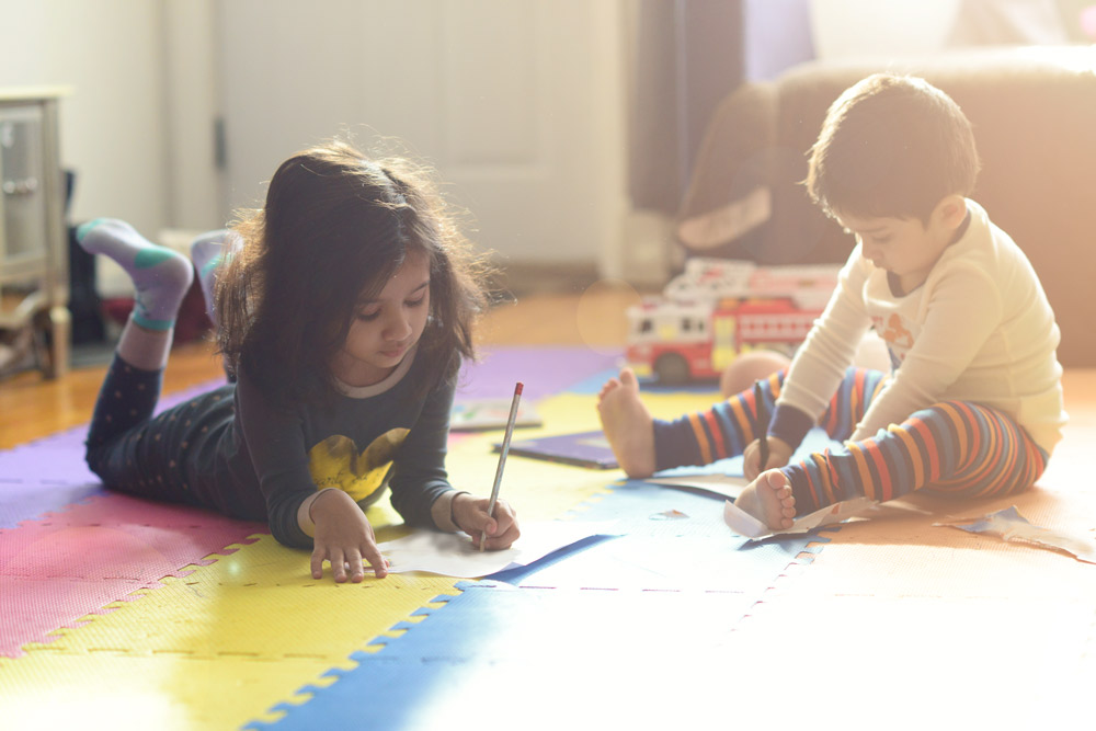 Little boy and girl on the floor, coloring
