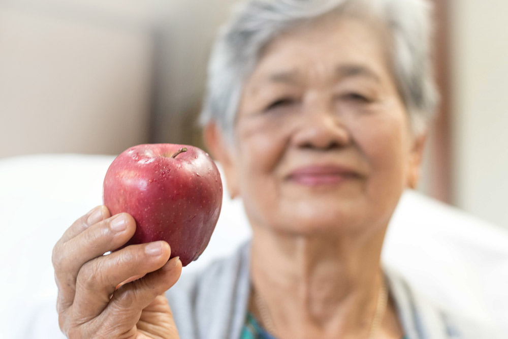 Older lady holding an apple