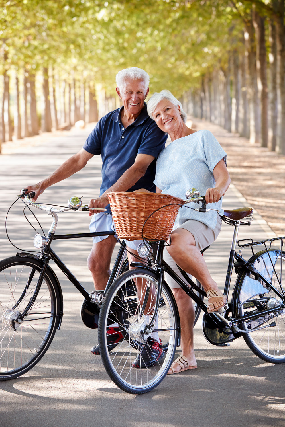 Older couple on bicycles on tree-lined path
