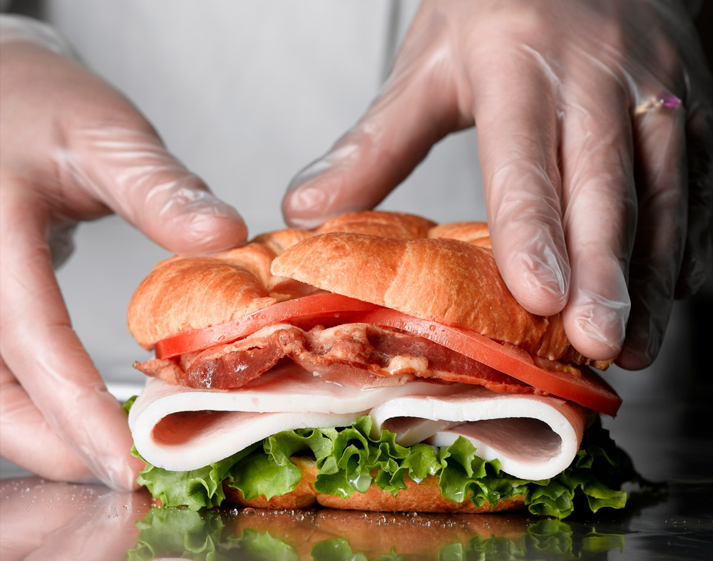 Gloved hands putting together a sandwich