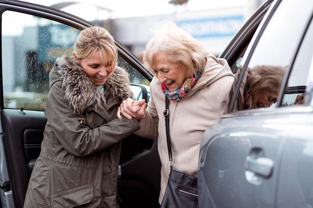 Woman helping older woman out of car